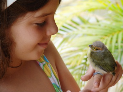 young girl with a baby bird perched on her finger